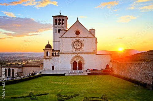 Photo Basilica of San Francis of Assisi with beautiful setting sun behind, Italy