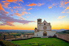 Basilica Of San Francis Of Assisi At Sunset Under Beautiful Glowing Orange And Blue Skies, Italy