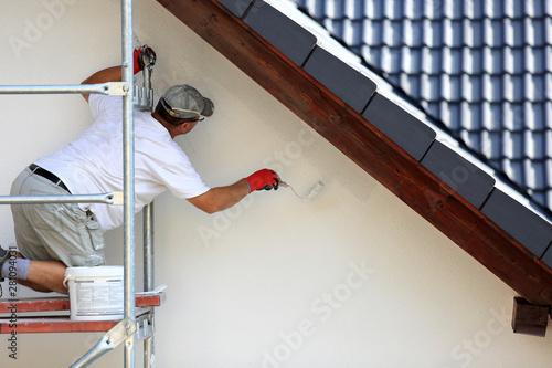 Foto  Malowanie wałkiem elewacji budynku na rusztowaniu.