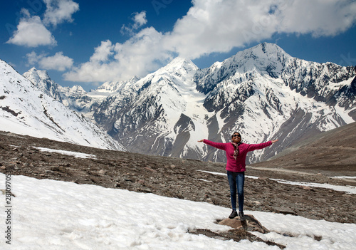 Teenage girl stretching arms with snowy Himalaya at backdrop