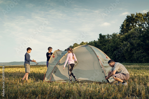 Obraz Family set up tent camp at sunset, beautiful summer landscape. Tourism, hiking and traveling in nature. - fototapety do salonu