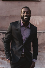 A Young Black Man In His Twenties Wearing A Suit In The City