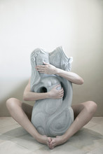 Woman Embracing Sculpture While Sitting On Ground