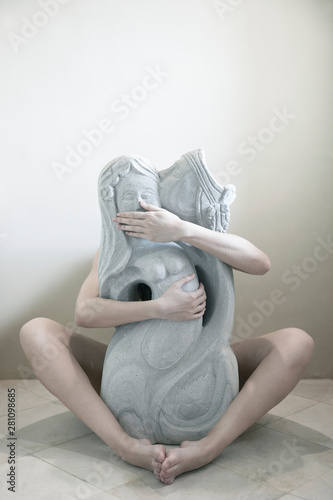 Foto op Canvas Historisch mon. Woman embracing sculpture while sitting on ground