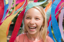 Girl Smiling In Front Of Rainbow Banner
