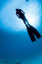 Silhouetted Diver Swimming Upw...