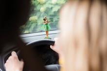 Woman Driving With Hula Girl On Dashboard