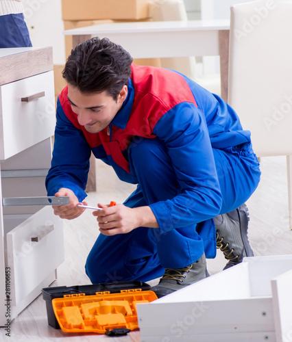Fotografia, Obraz  Contractor repairman assembling furniture under woman supervisio