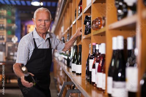 Pinturas sobre lienzo  Owner of wine shop taking wine bottle from shelf