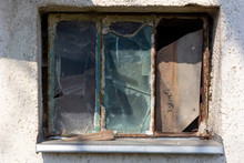 A Rusty Window With Broken Glass Panes