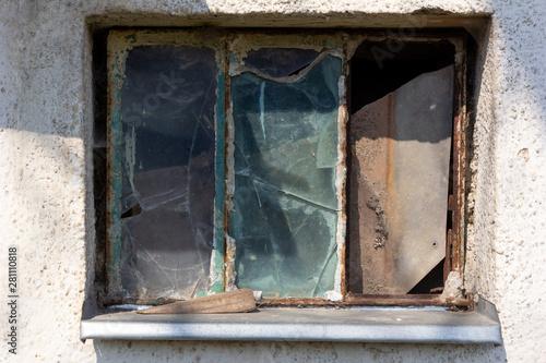 Fototapeta A rusty window with broken glass panes