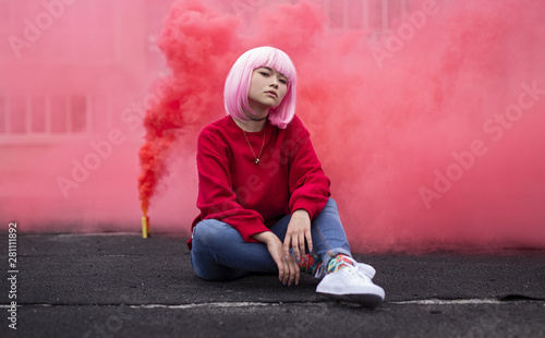 Female hipster sitting near red smoke - 281111892