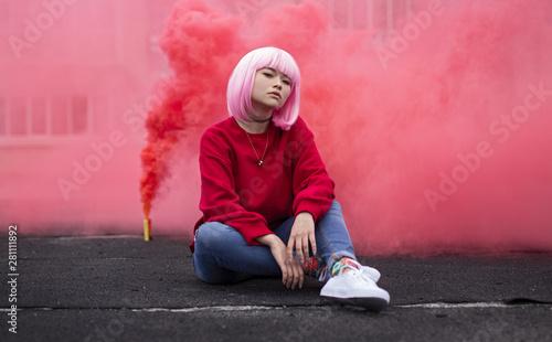 Foto  Female hipster sitting near red smoke