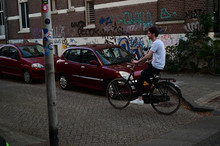 Dutch Student Riding On His Bicycle Through An Old Dutch Street With Grafitti On The Walls