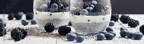 panoramic shot of yogurt with chia seeds and berries in glasses near scattered s Fototapete