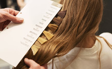 Stylist Choosing Color From Hair Samples For Woman In Salon