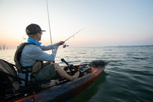 Young Man Kayak Fishing At Sun...