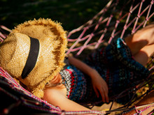 Relaxed Young Woman With Sun Hat Daydreaming In Hammock.