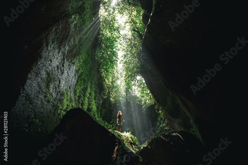 Young girl Girl stands under the ray of light in the cave in Bali, indonesia. Tukad Cepung waterfall