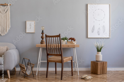 Fotografie, Obraz  Stylish and design home interior of living room with gray sofa, wooden cube and desk, books, plants, mock up poster frame, macrame and elegant accessories