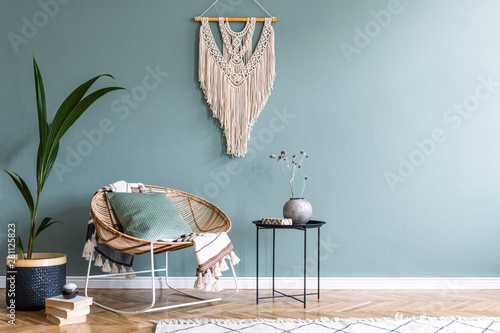 Canvas Prints Countryside Stylish minimalistic interior of living room with design rattan armchair, black coffee table, tropical platn in basket, beige macrame on the wall and elegant accessories. Eucalyptus color of wall.