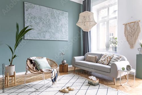Obraz Boho style living room with macrame, rattan armchair and sofa - fototapety do salonu