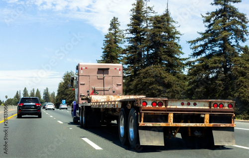 Fotografía Semi truck on highway with empty flatbed trailer.