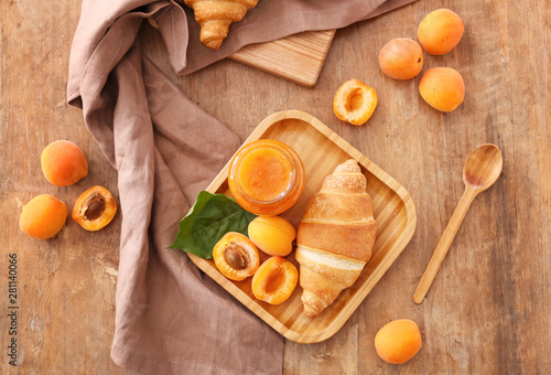 Foto Plate with tasty apricot jam and croissant on wooden table