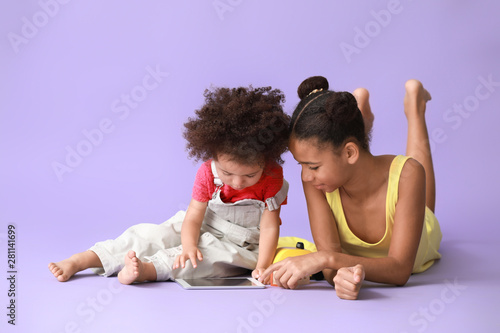 Valokuva  Cute African-American sisters with tablet computer watching cartoons on color ba
