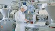 Young Male Quality Supervisor or Food Technician is Inspecting Automated Production at a Dumpling Food Factory. Employee Uses a Tablet Computer for Work. He Wears a White Sanitary Hat and Work Robe.