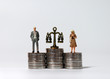 canvas print picture - Miniature people standing on a pile of coins of the same height.