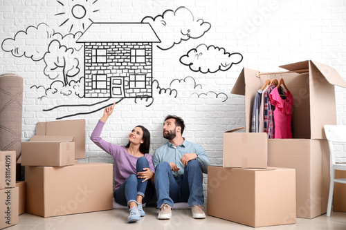Young couple with belongings dreaming about moving into new house