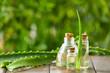 Bottles of aloe vera essential oil on wooden table