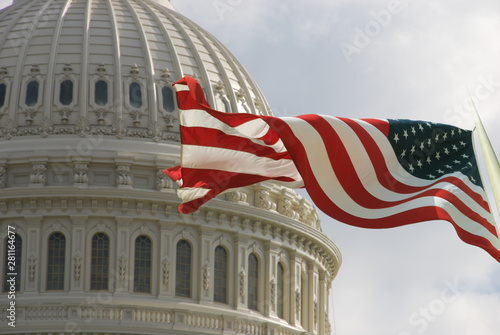 Obraz Beautiful flag of the United States of America waving with the strong wind and behind it the dome of the Capitol. - fototapety do salonu
