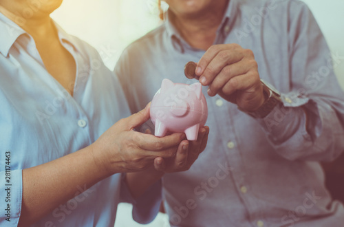 Fotografía  Senior couple hands putting coin to piggy bank for retirement together,Saving mo