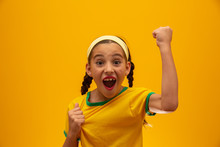 Football Supporter, Brazil Team. World Cup. Beautiful Little Girl Cheering For Her Team On Yellow Background