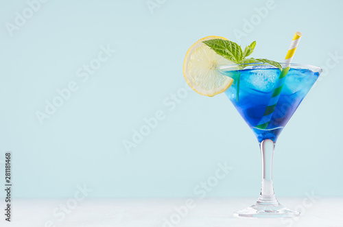 Fotografía  Bright summer fresh blue fruit cocktail with blue curacao liquor, ice cubes, lemon slice, green mint in pastel mint color interior on white wood board