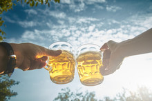 Pair Holding Beer Glasses In T...