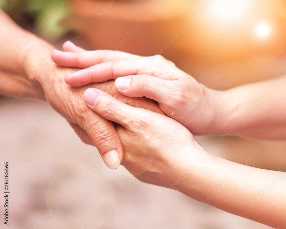 Fototapeta Caregiver, carer hand holding elder hand in hospice care. Philanthropy kindness to disabled concept.