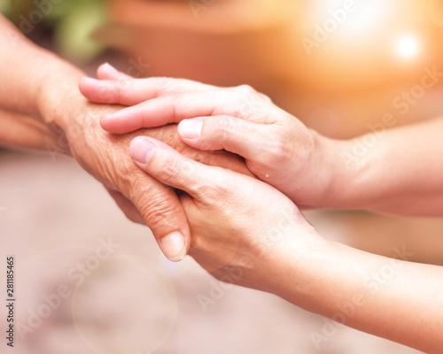 Fotografia Caregiver, carer hand holding elder hand in hospice care