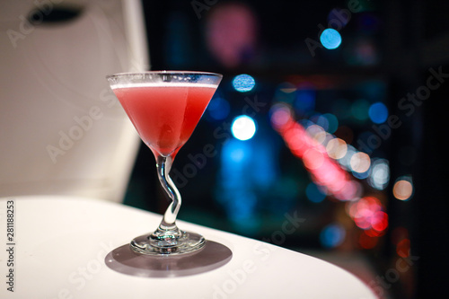 blur image of cocktail glass with city view at night