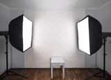 Interior of modern photo studio with  professional equipment ,white brick wall background