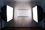 studio lighting, white monitor on a white brick wall