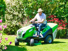 Senior Man Driving A Tractor Lawn Mower In Garden With Flowers