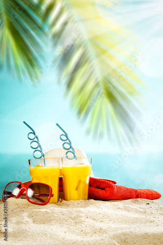 Table background with orange ice juice in a glass on a wooden table top with beautiful blue sky and ocean and palm tree view. - 281194825
