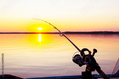 Poster de jardin Montagne Fishing rod spinning with the line close-up. Fishing rod in rod holder in fishing boat due the fishery day at the sunset. Fishing rod rings. Fishing tackle. Fishing spinning reel.