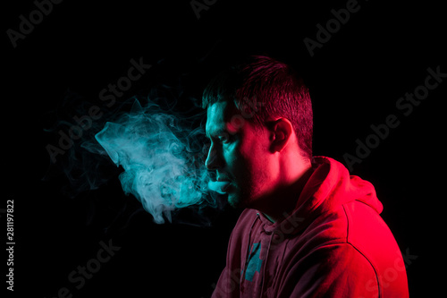 Fotografija  Close up portrait of the face of an adult serious man exhales green toxic smoke while smoking e-cigarette and vape illuminated with blue and red colored light on a black background