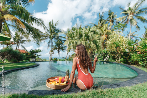 Deurstickers Ontspanning Breakfast tray in swimming pool, floating breakfast in luxury hotel. Girl relaxing in the pool drinking smoothies and eating fruit plate, smoothie bowl by the hotel pool. Exotic summer diet. Tropical