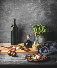 Still Life With Italian Caprese Salad Served On Rustic Table With Potted Basil Kitchen Herbs And Bottle Of Olive Oil On Rustic Table With Ingredients