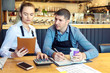 canvas print picture - Small family restaurant owners discussing finance calculating bills and expenses of their new small business.